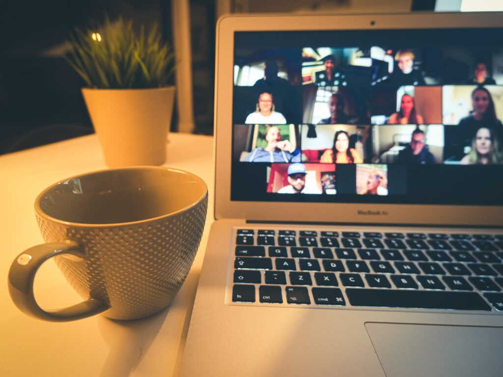 Computer showing online meeting and coffee cup